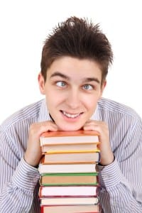 Image of a cross-eyed boy with books to express overwhelm with a language learning project