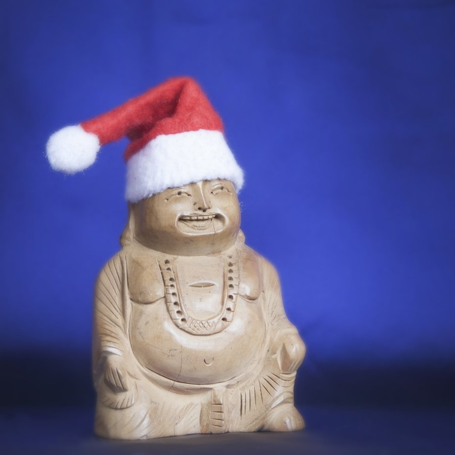 Image of a wooden Buddha with Santa Claus hat