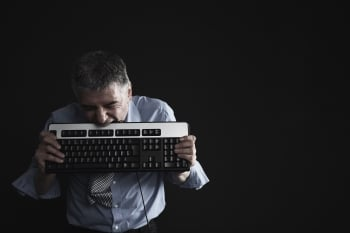 Image of a man with low attention span biting a keyboard