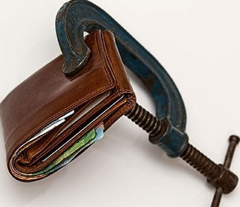 Image of a wallet clamped in a vice to illustrate a concept relating to debt and negative effects on memory