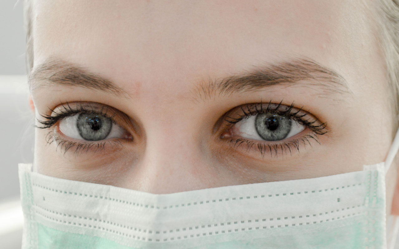 Woman in surgical face mask. Protective masks aren't recommended for healthy individuals.