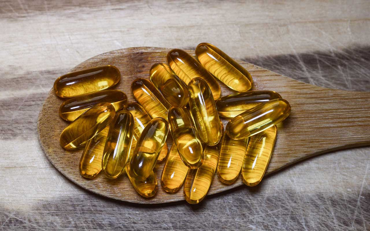 Fish oil capsules in a wooden spoon.