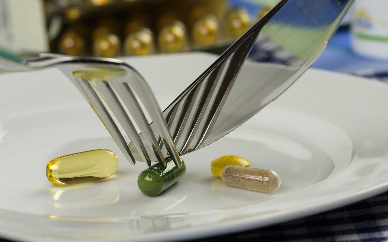 Vitamin supplements on a plate, being cut by a fork and knife.