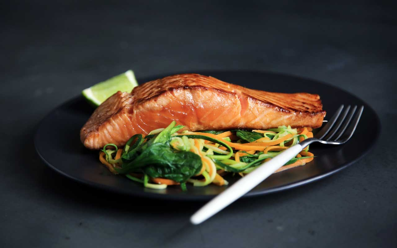 Salmon and vegetables on a plate, part of a memory-healthy diet.
