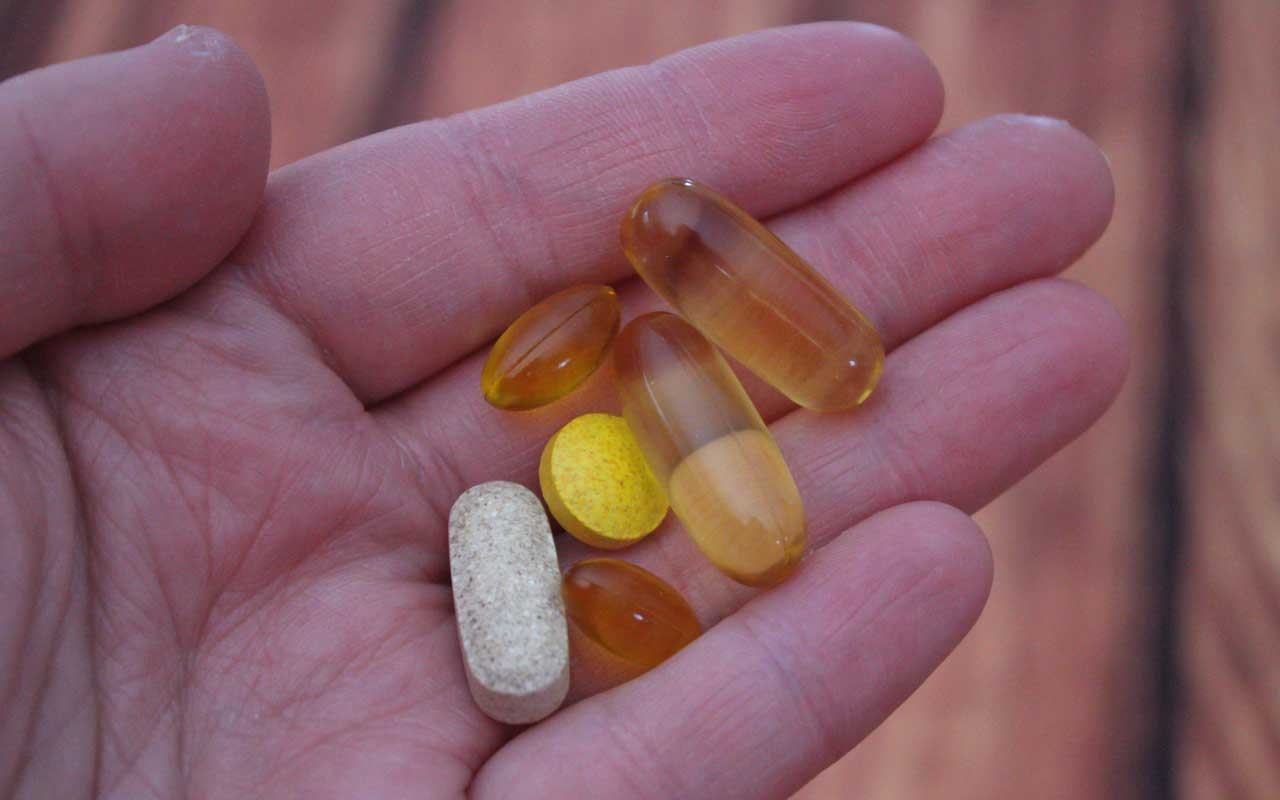 Vitamin supplements in a person's hand, in capsule and tablet form.