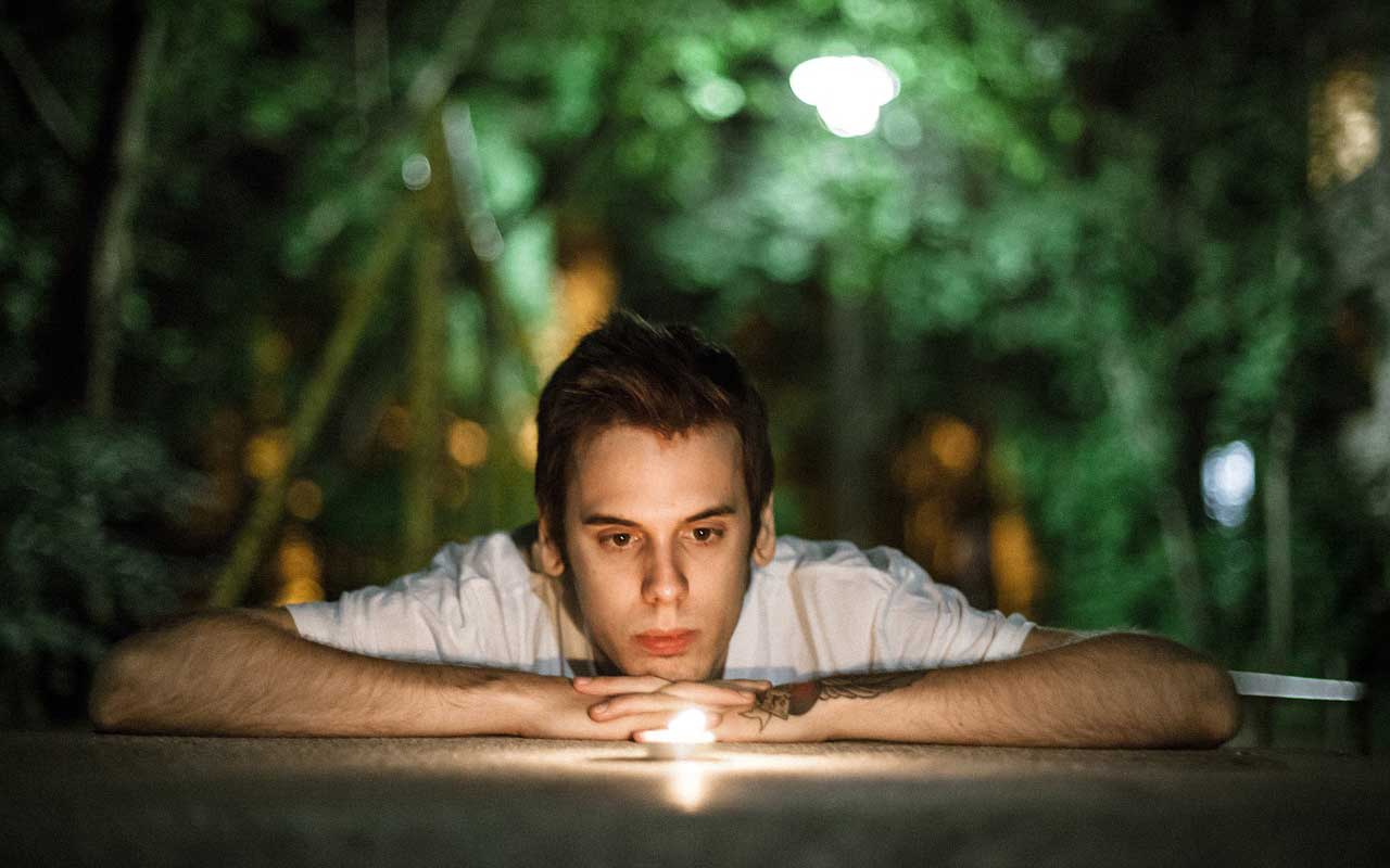 A man stares into a candle, a type of concentration meditation with an object focus.