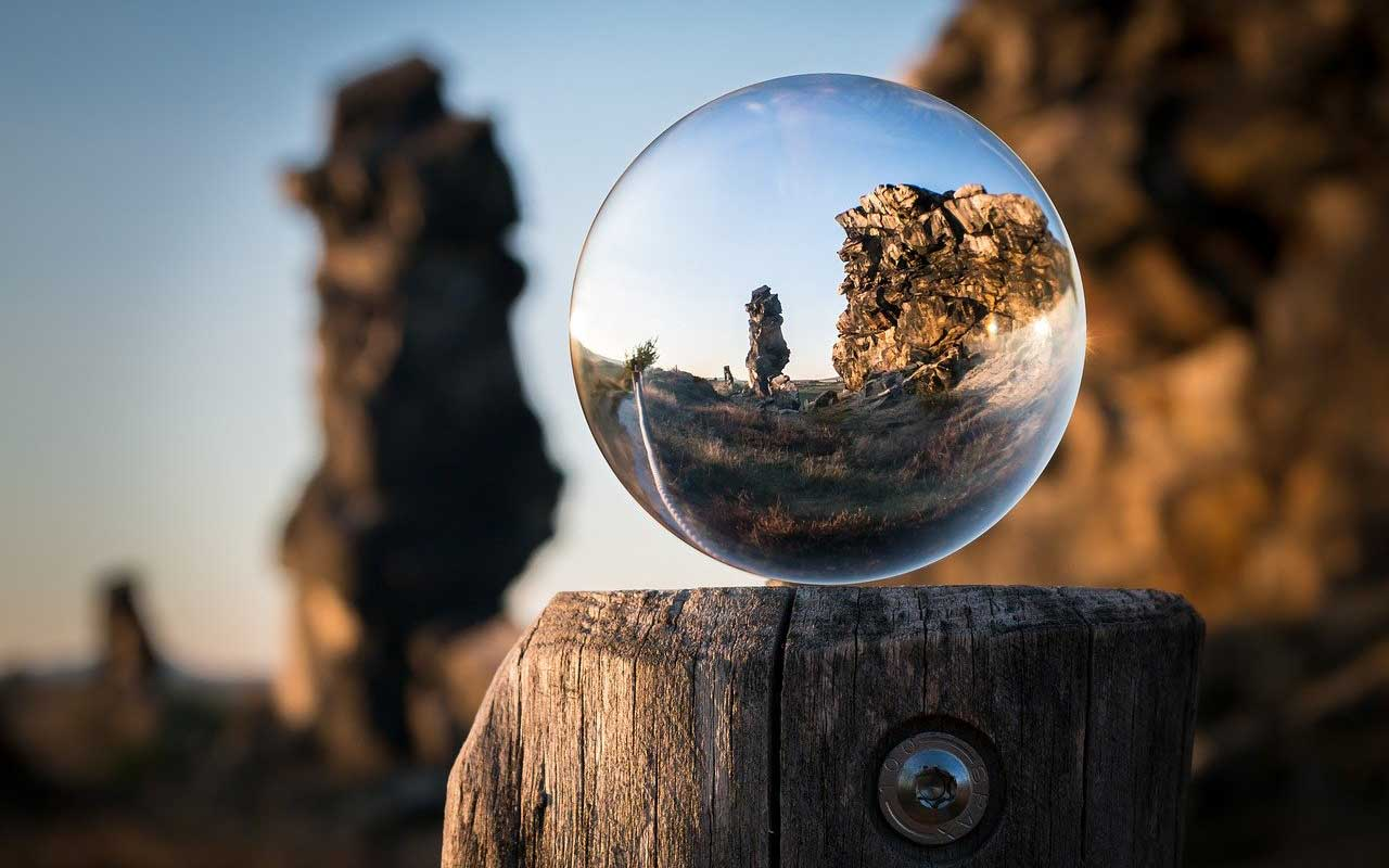 Memorizing a song creates focus and concentration. Picture of a clear globe on a post, looking out at a rock formation.