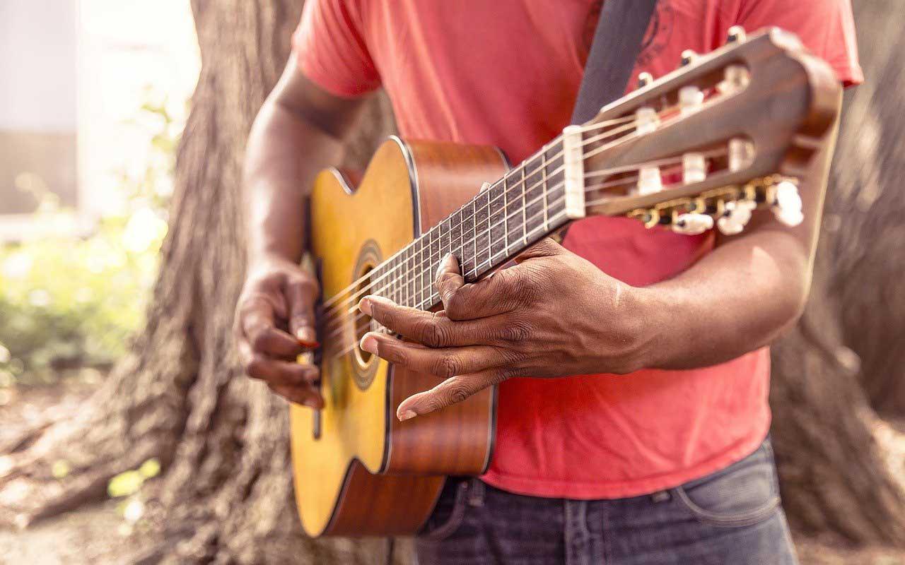 A man plays the guitar as he learns how to memorize lyrics.