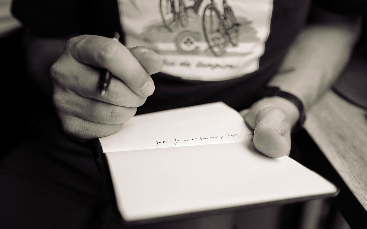 A person writing in a journal, a key to testing how to memorize song lyrics.