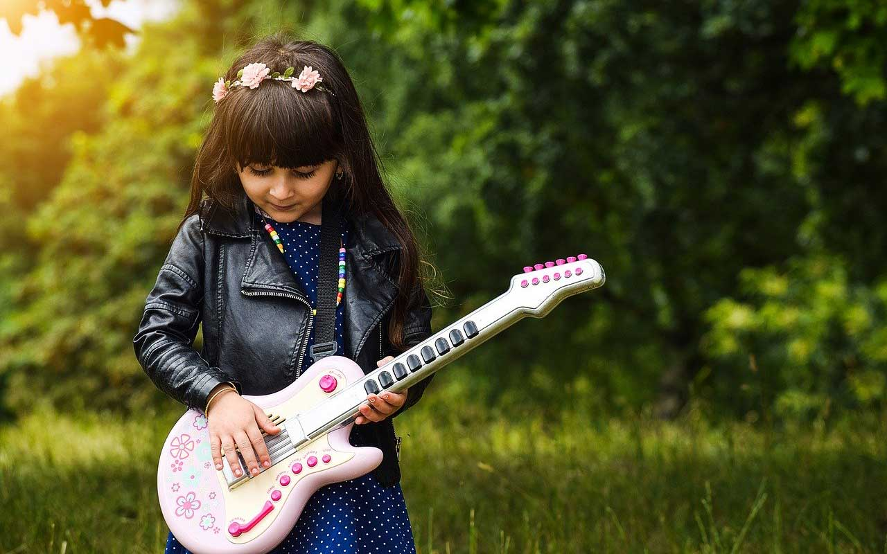 A girl with a leather jacket and flowers in her hair plays a pink plastic guitar.