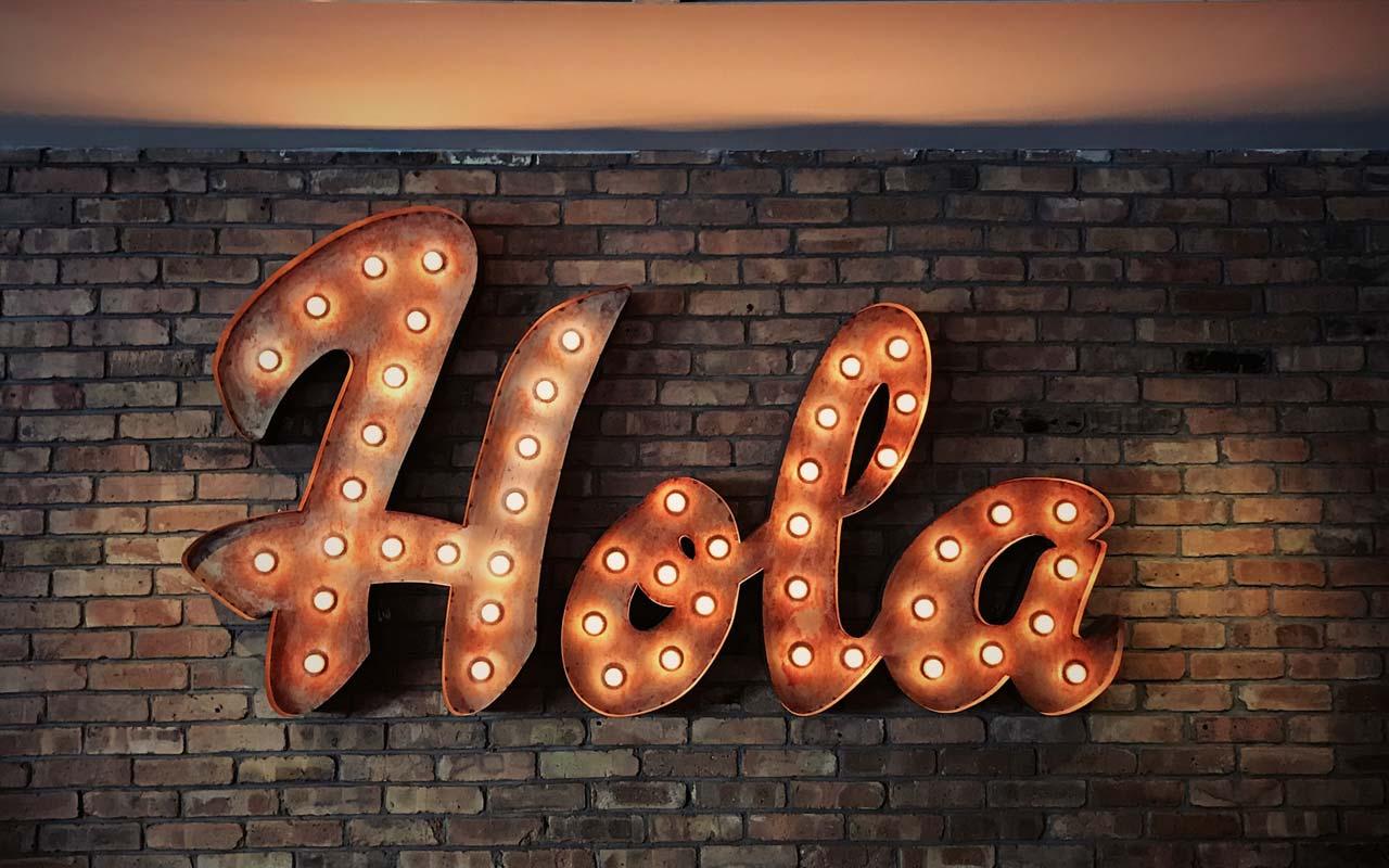 """An illuminated sign says """"hola"""" against a brick wall."""