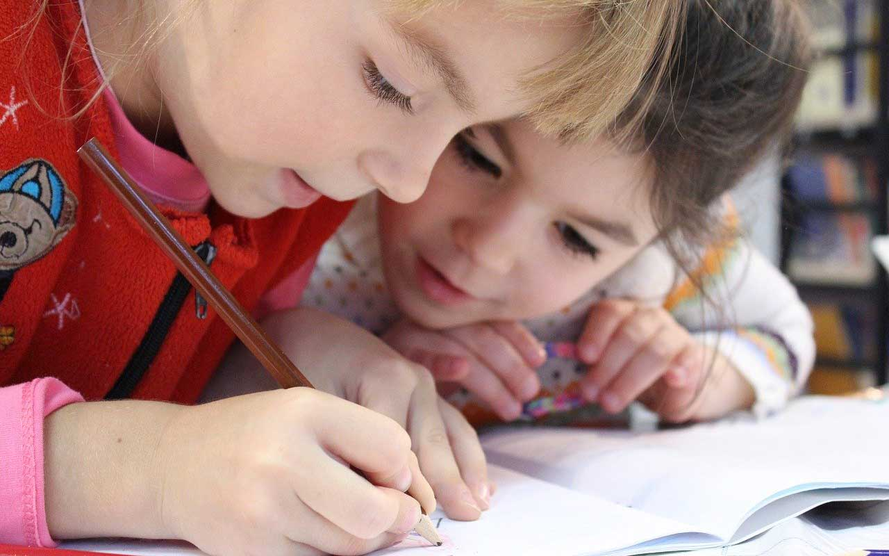 Two children focusing on a coloring book.