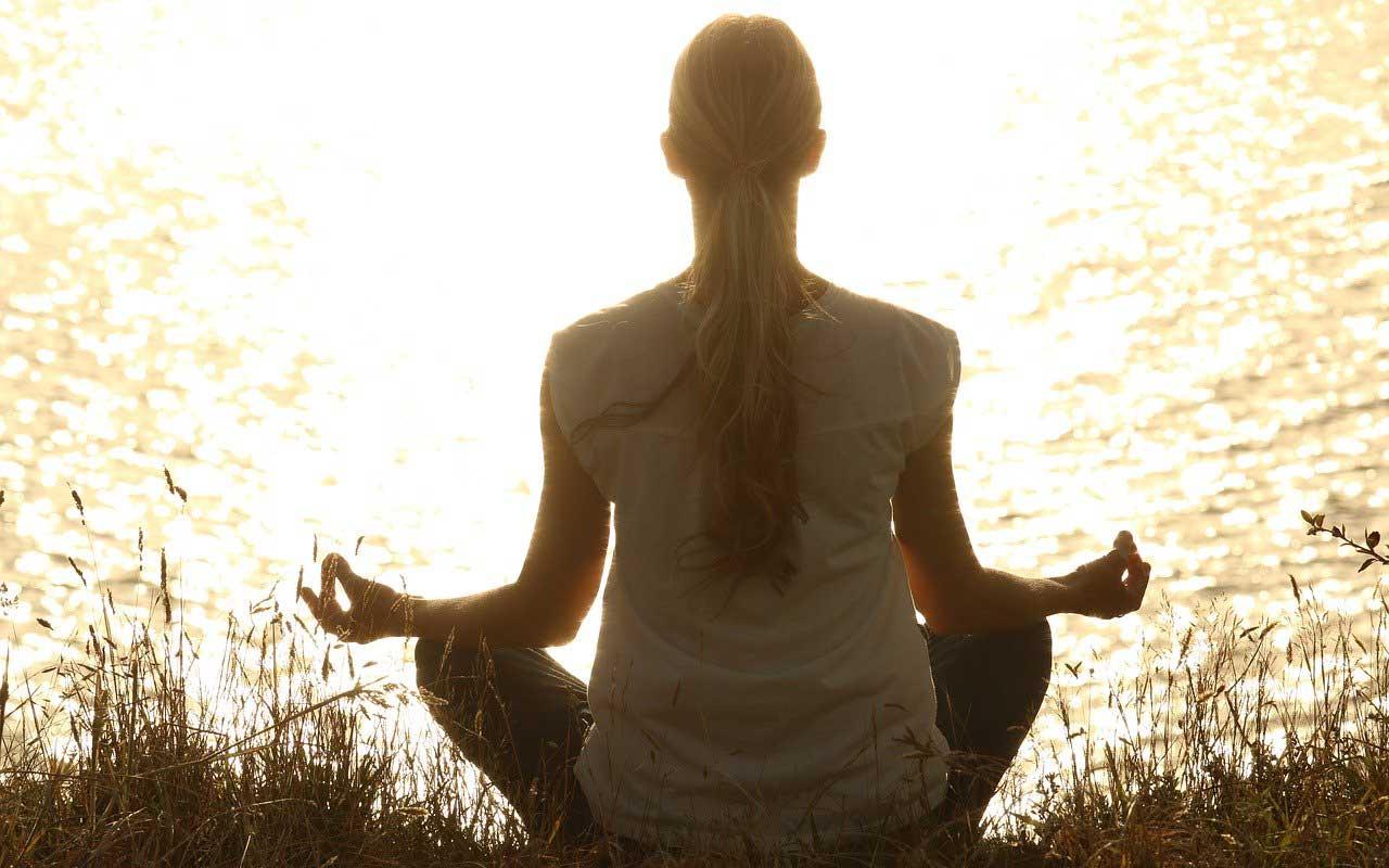 A woman sitting by a lake practicing mindfulness meditation.