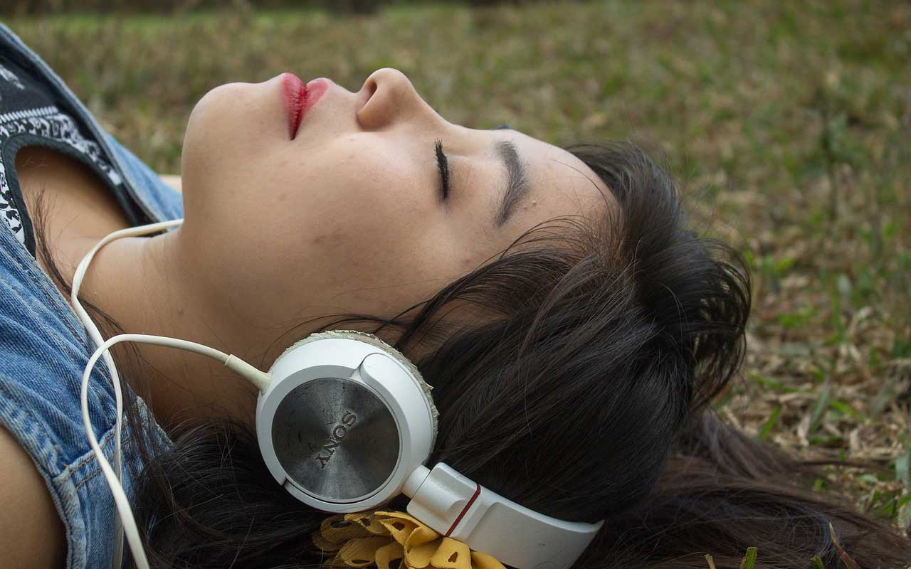 A woman wearing large headphones lays in the grass with her eyes closed, focusing on the music.