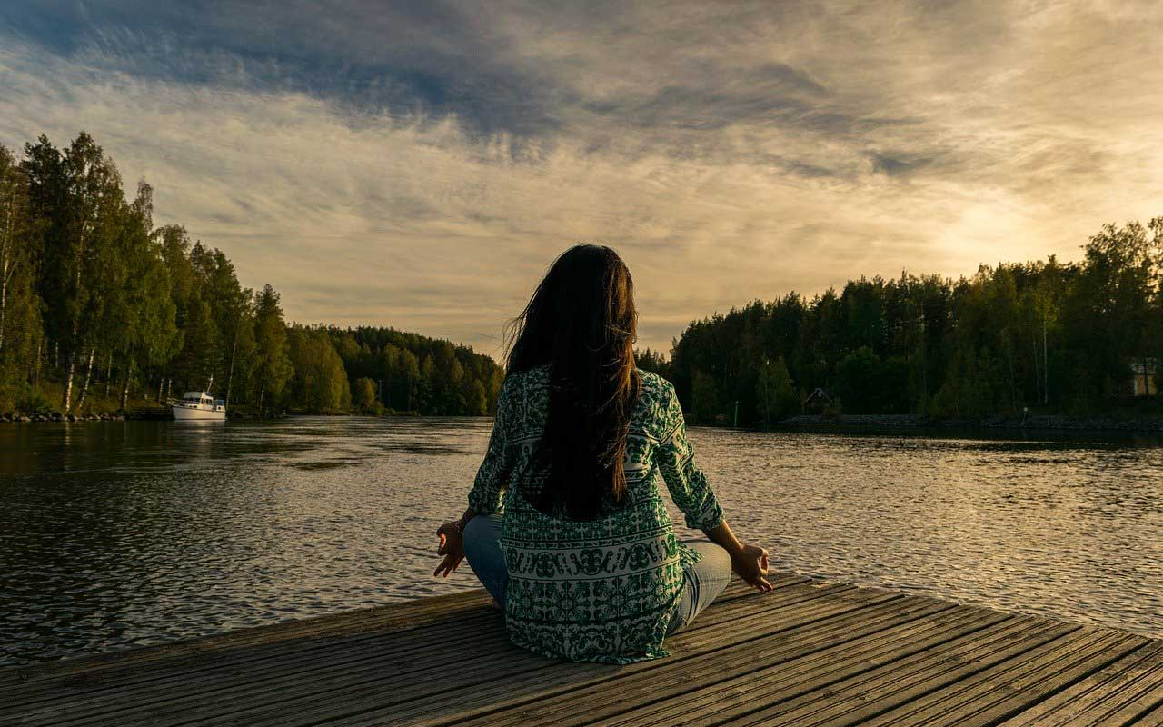 A woman meditating at the lake, practicing mindfulness.
