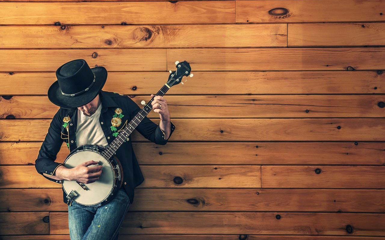 A musician with a banjo leaning against a wooden wall, learning how to memorize song lyrics.