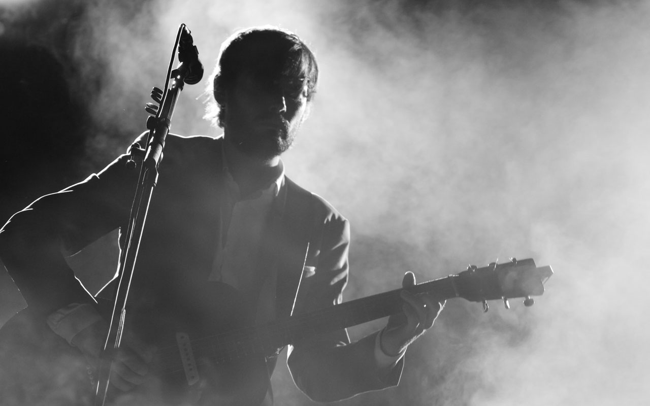 A man plays the guitar at a microphone in a cloud of smoke.