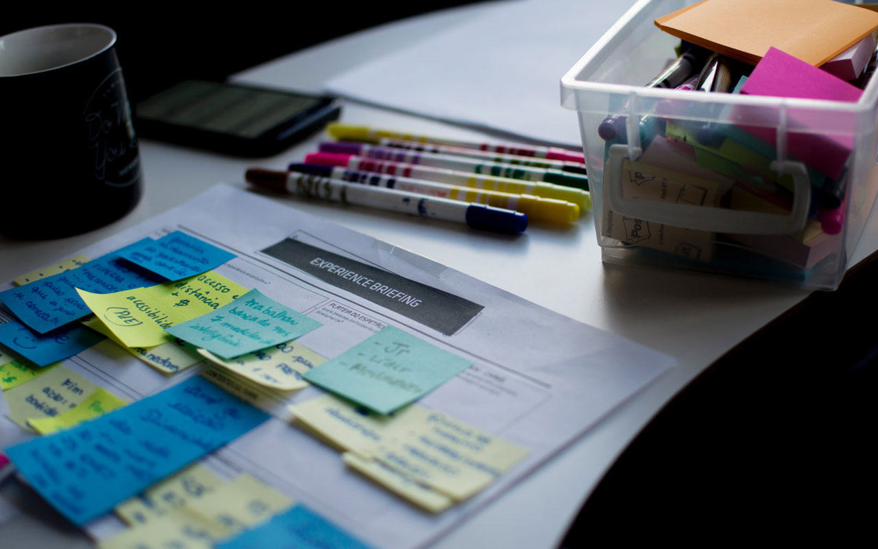 What is mind mapping? It can be used when you need to understand a project better. This image shows a desk with sticky notes, markers, and other office supplies.