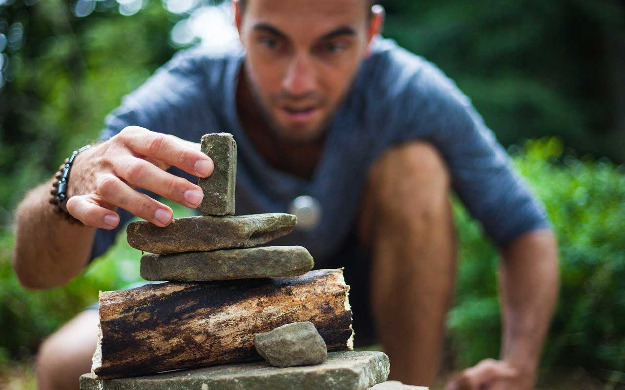A man focused on stacking stones.