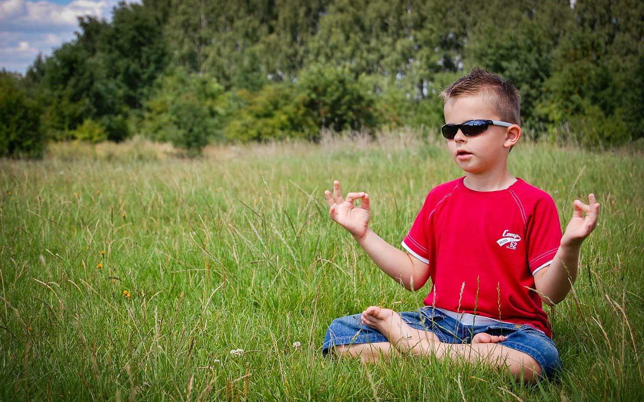 A young boy sits in the grass with sunglasses on, with his hands in a meditation mudra (hand gesture).