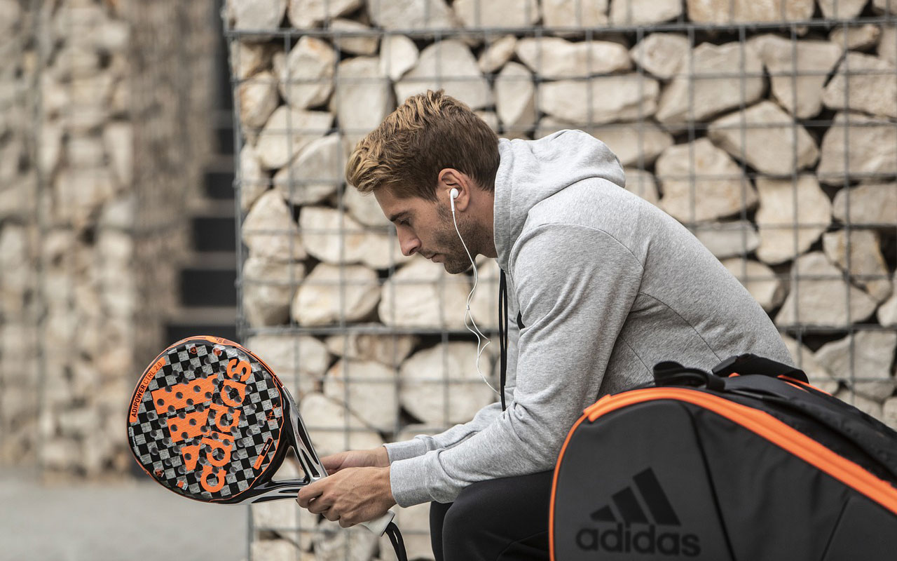 A tennis player holds his racquet, waiting for a match to start.