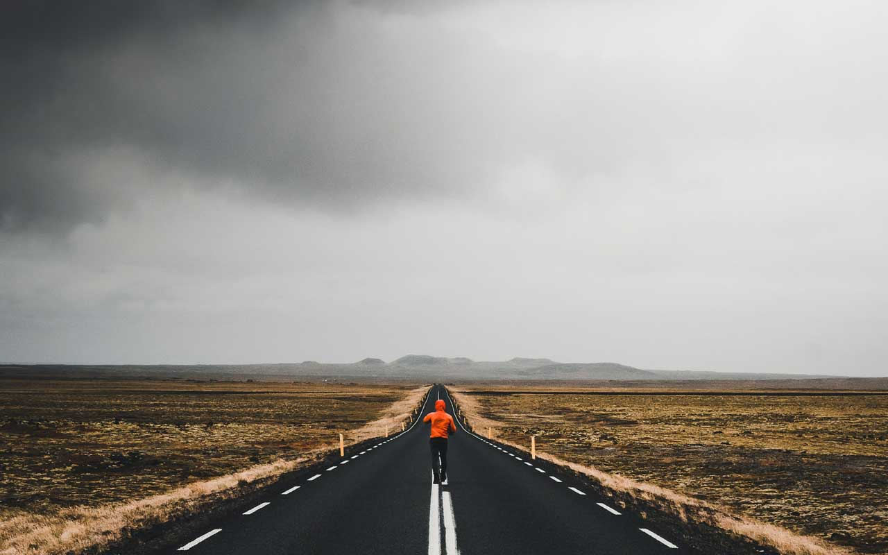 A person in an orange raincoat walking down the center line of a highway with storm clouds on the horizon.
