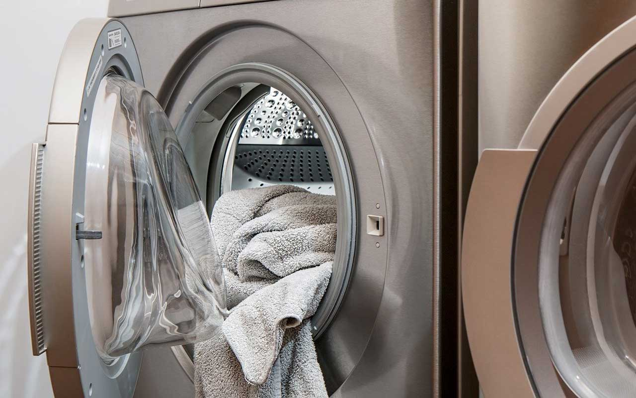 A clothes dryer with clean towels spilling out.