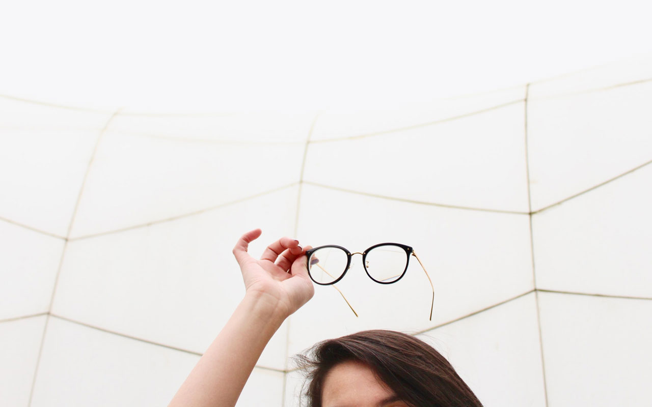 A woman holds a pair of reading glasses above her head. Forgetting what reading glasses are for would be an indicator that memory disorders might be to blame.