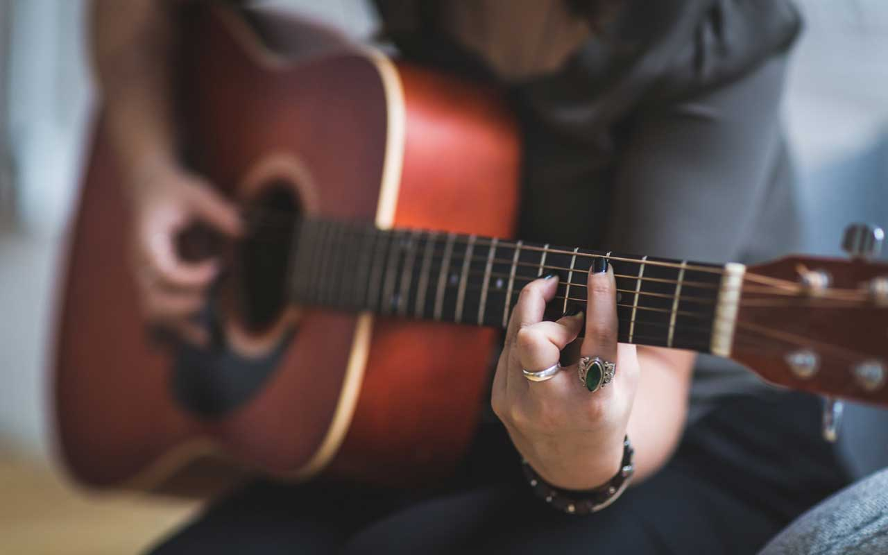 A person plays guitar, a long-term learning project that could help you work with focus.