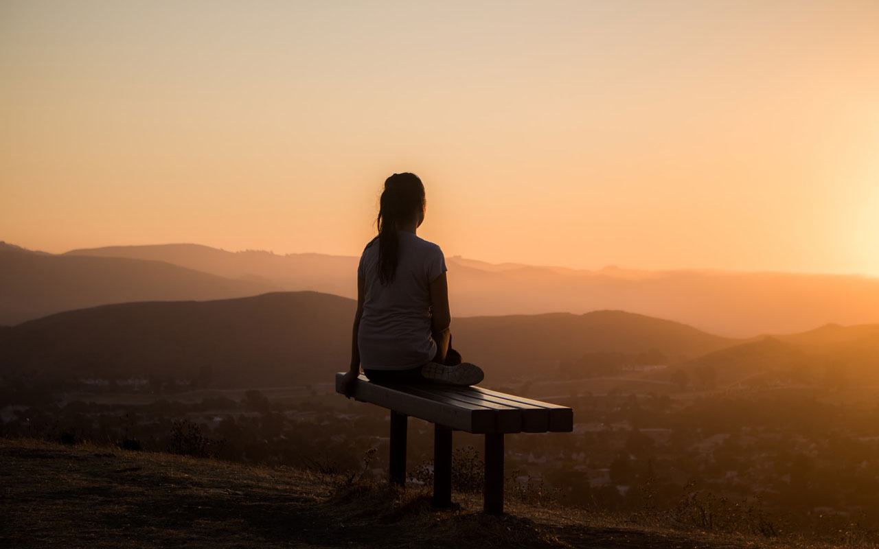 A woman on a bench overlooking a sunrise, using concentration meditation to help her focus on work.