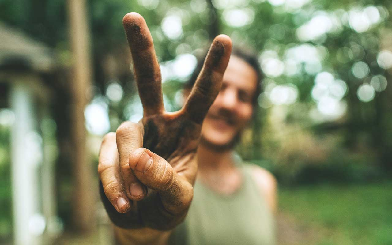 "A person holds up a ""peace"" sign, with their pointer and middle fingers raised."