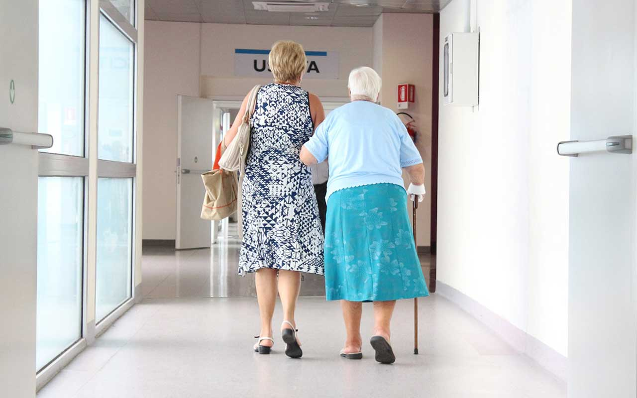 A woman walks her elderly mother through a medical facility. Early diagnosis of memory disorders can help caregivers and patients cope with their disease.
