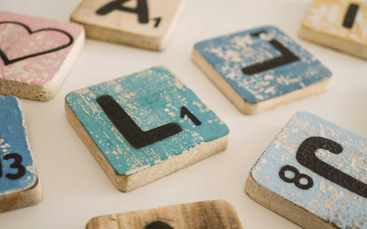 Hand painted Scrabble letters. Word games like Scrabble can help improve comprehension.
