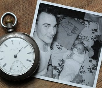 A black and white photo of a man and a baby, with a pocket-watch sitting beside the photo.