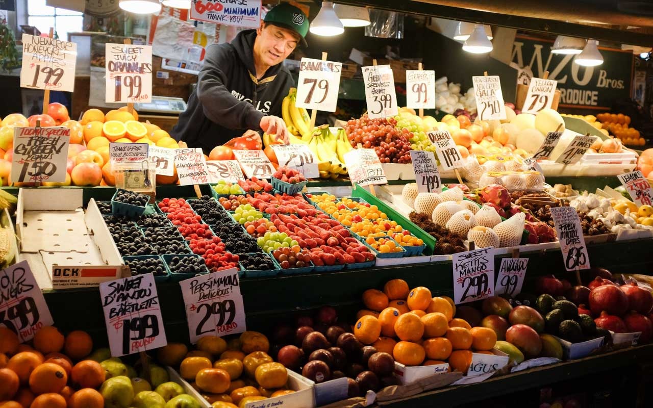 A man restocks produce at a market.