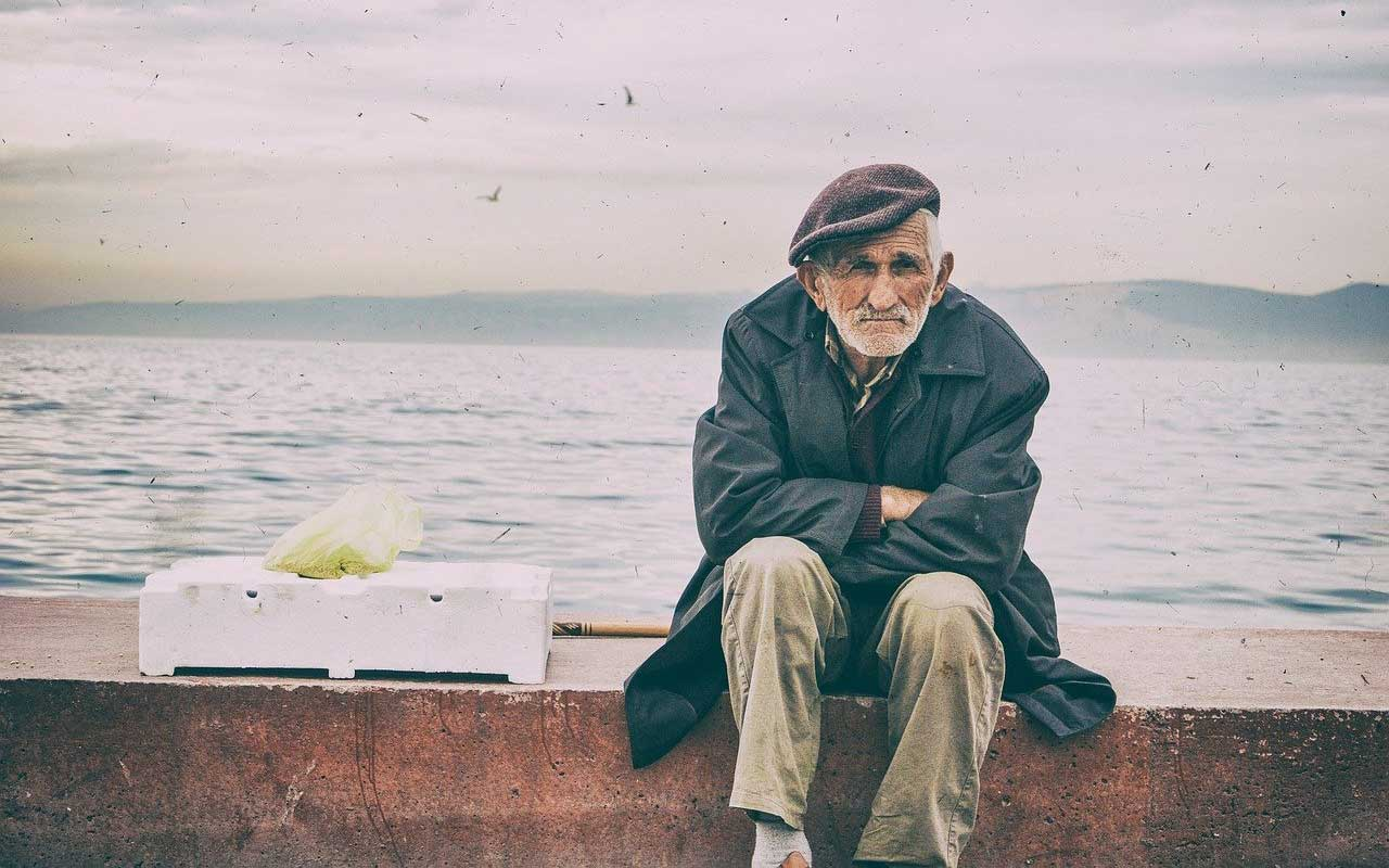 An old man sits on a sea-wall.