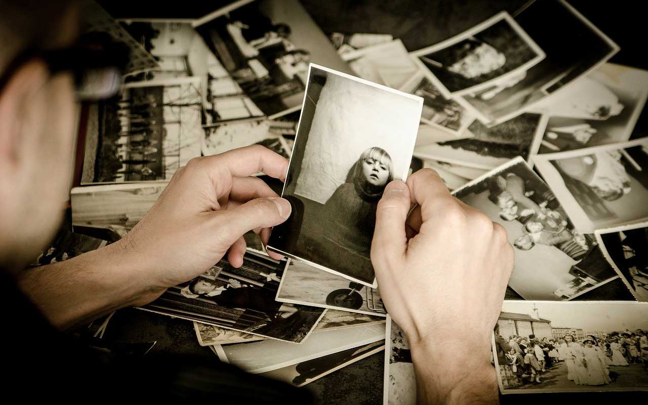 A person holds an old sepia-toned photo of a young girl. Memory loss can make it difficult to remember even close family members.
