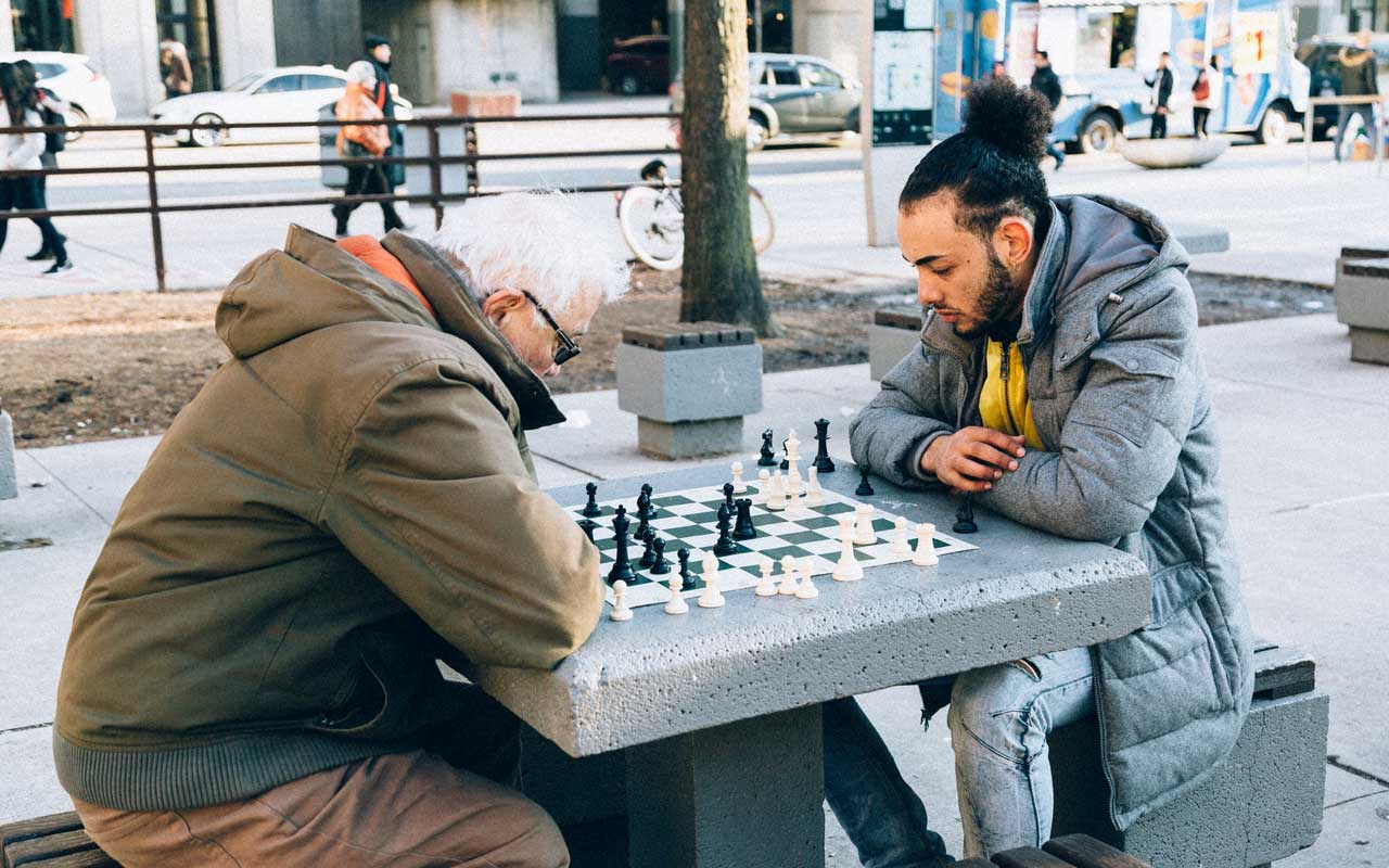 An older man plays chess in the park with a younger man. Chess is one type of cognitive activities for adults that may be beneficial as you age.