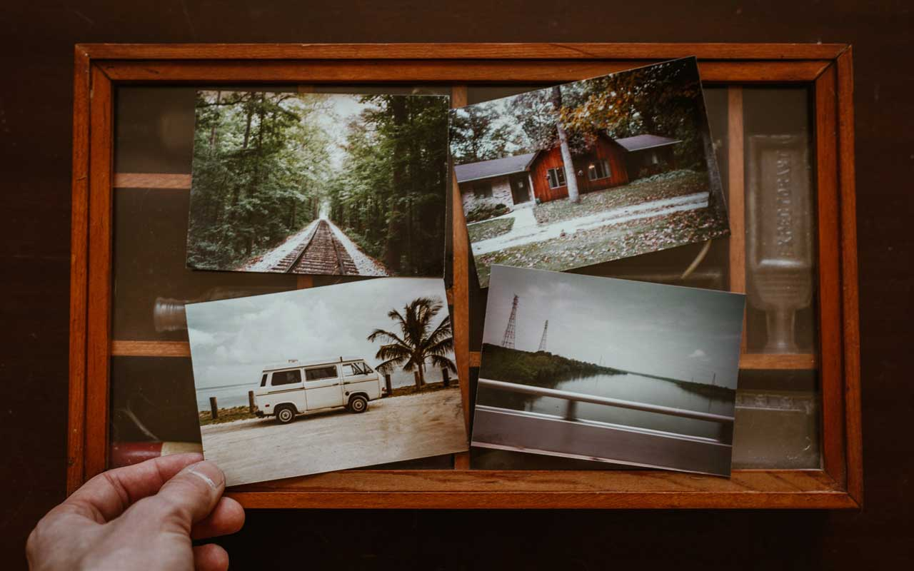 A shadow-box with four travel photos sitting on top.