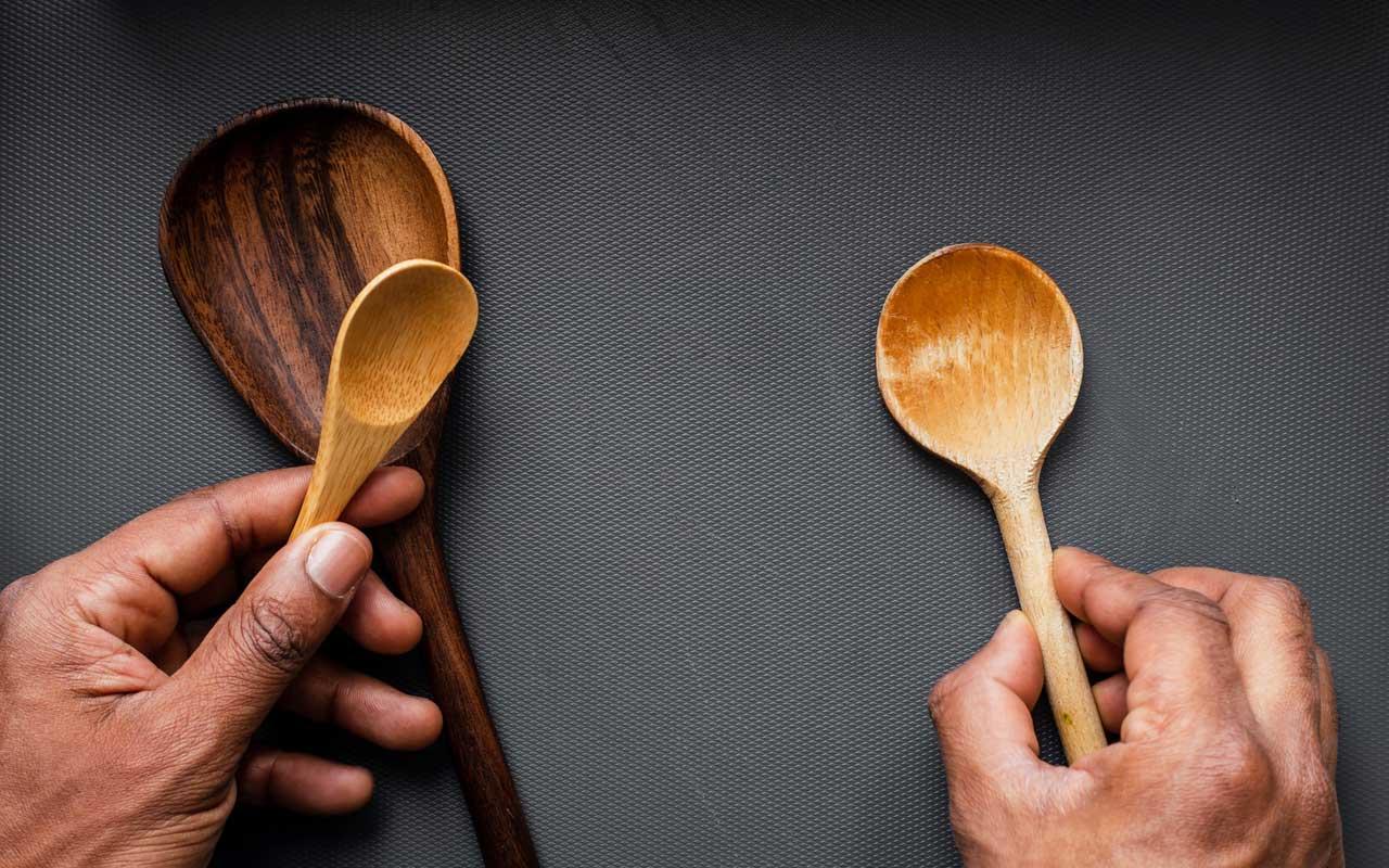 A person holds wooden spoons in their hands, spaced apart on a table.