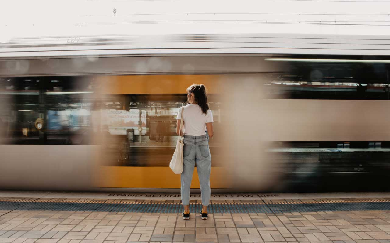 A woman watches a train speed by.