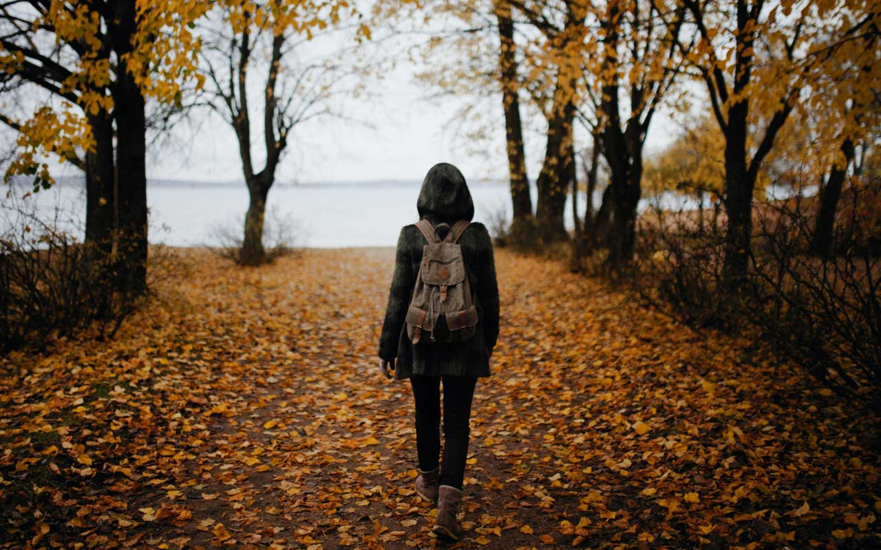 A person walks along a leaf-covered road. Mindful walking like this can be a good cognitive activity for adults.