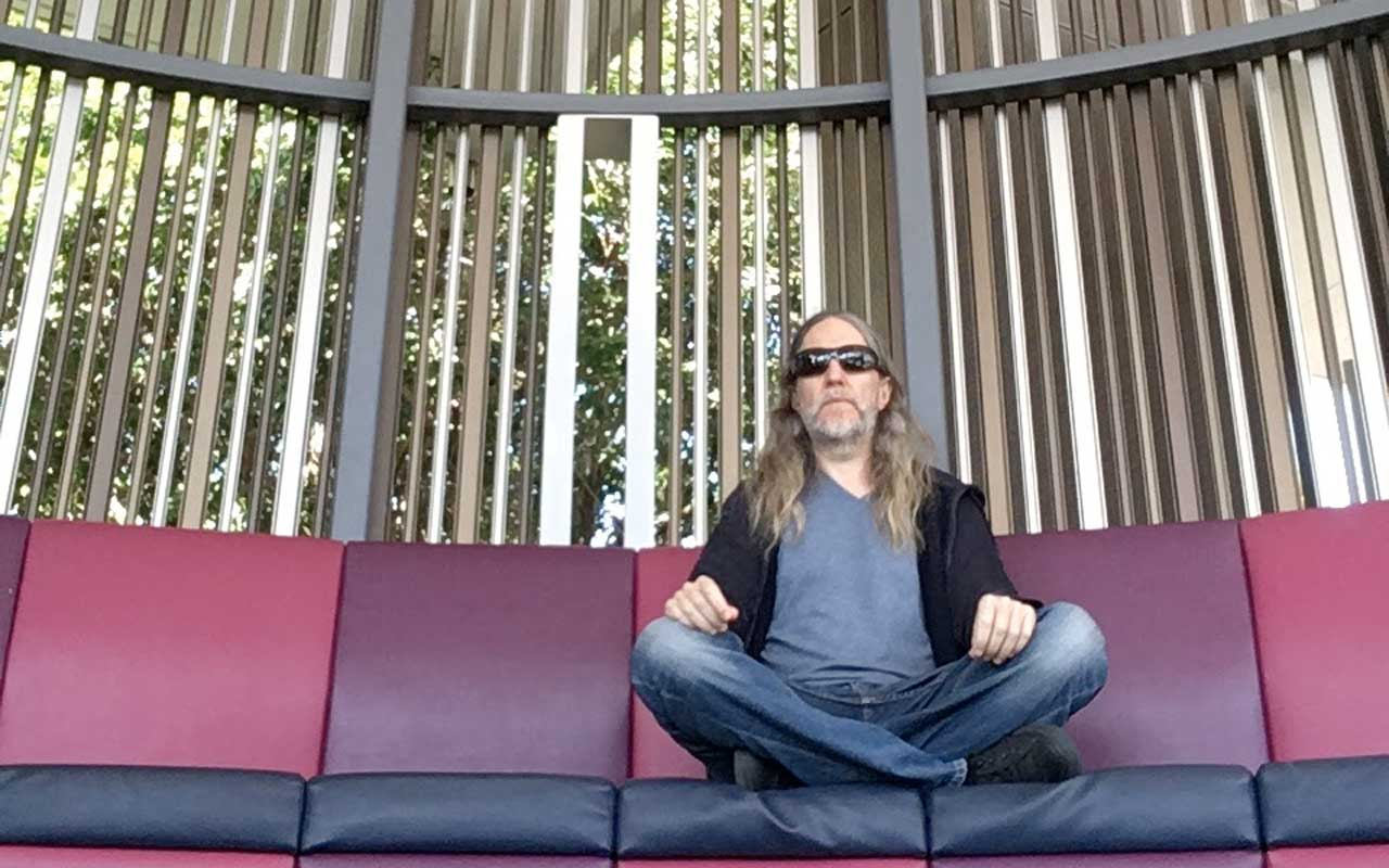 Anthony sits in meditation at his local university campus, practicing visualization meditation.