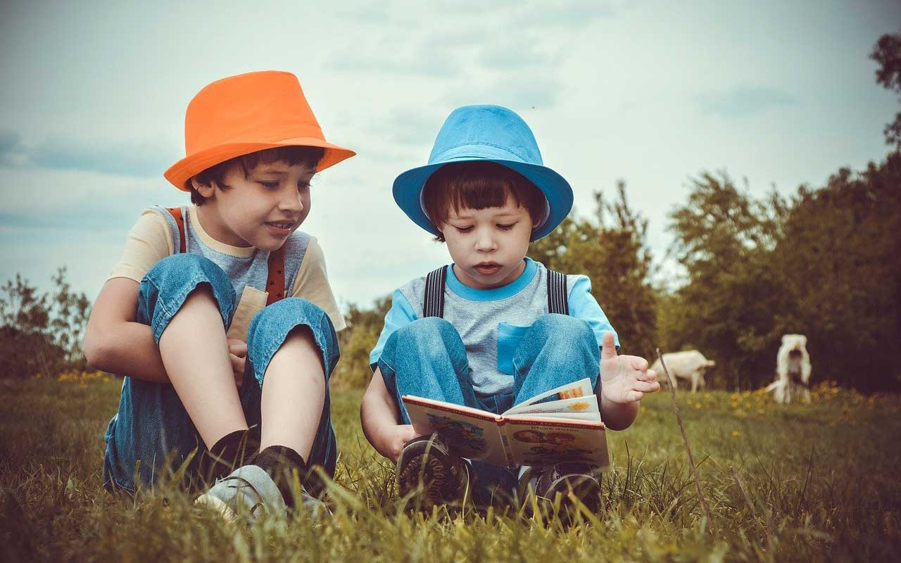Two young brothers read out loud from a book while sitting in the grass.