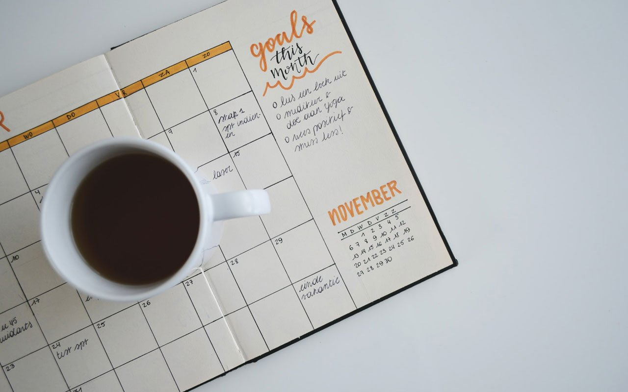 A goals calendar with a cup of coffee sitting on top.