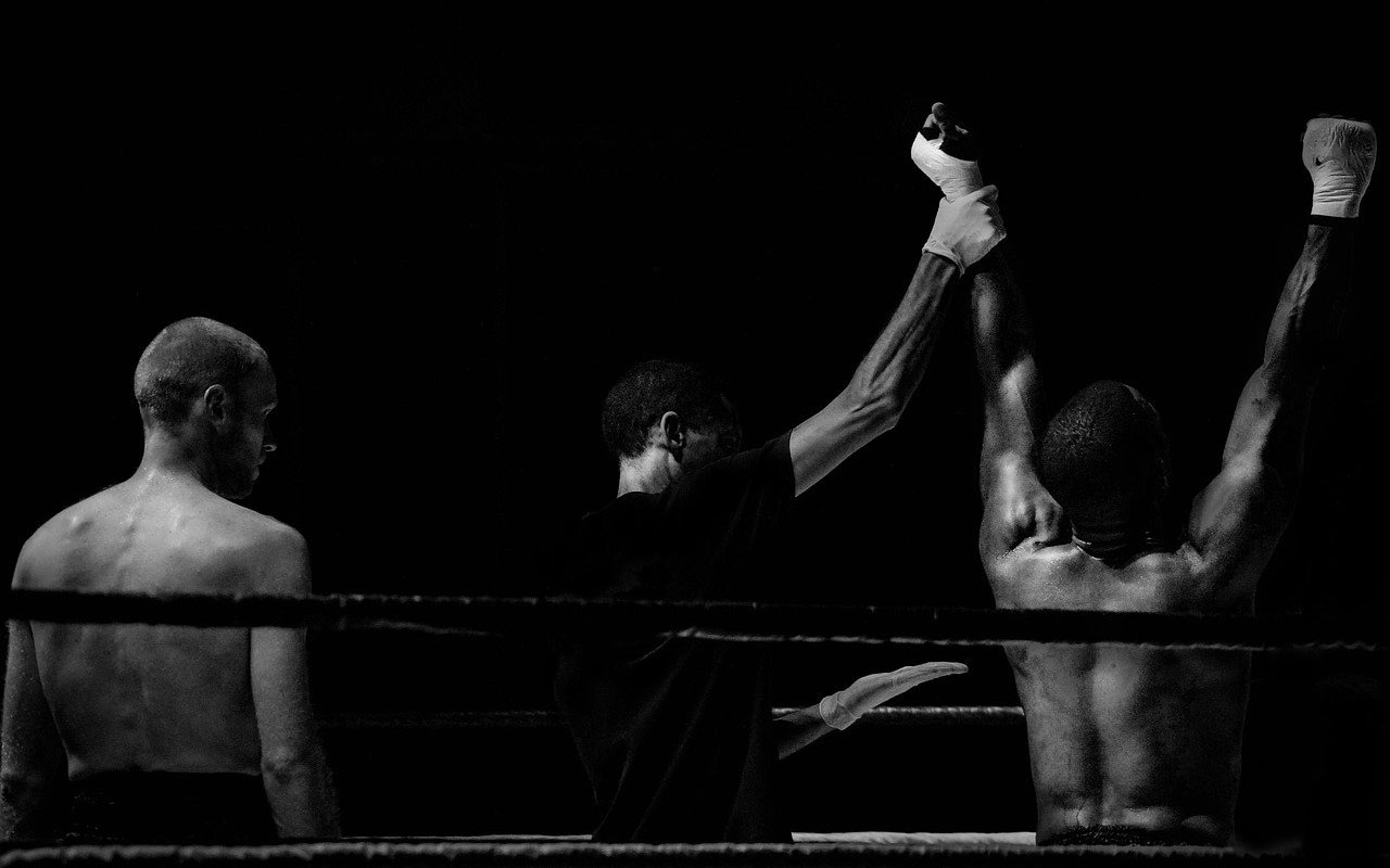 A referee holds up the arm of a victorious boxer.