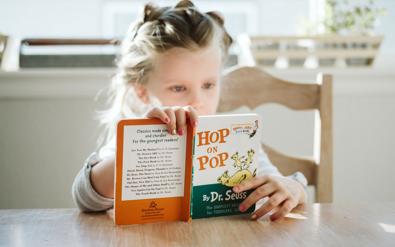 A young girl reads the book Hop on Pop by Dr Seuss, aiding her cognitive function development.