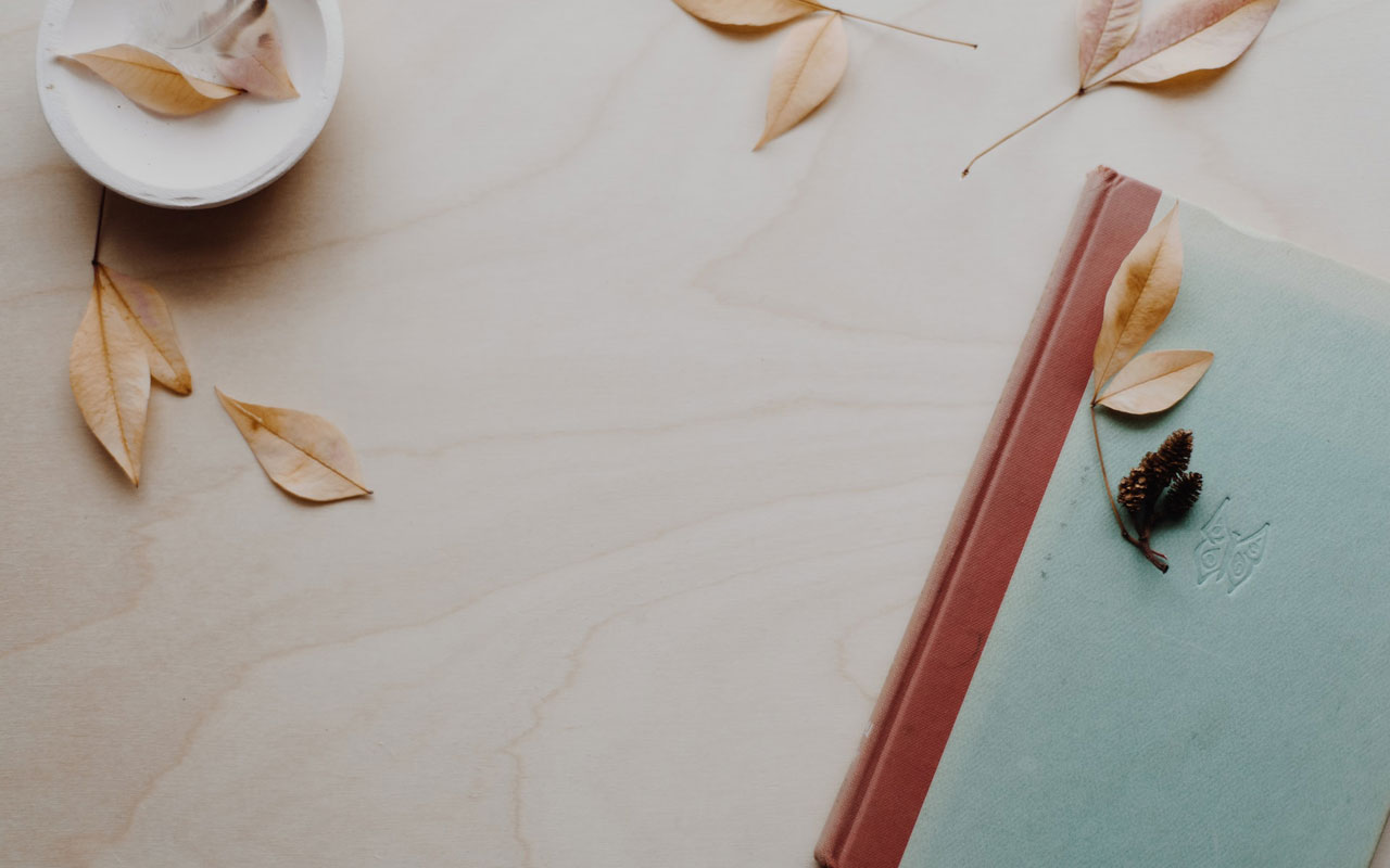A journal on a wooden table. Journaling is a key component of successful guided visualization meditation.