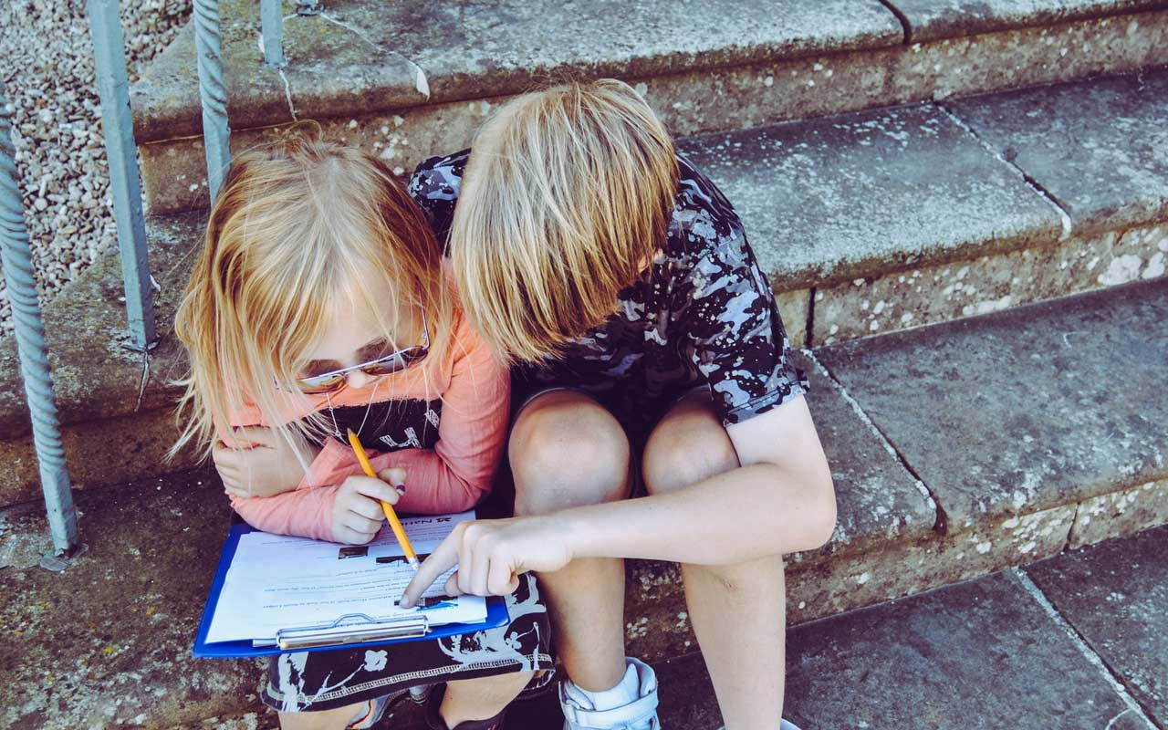 Two children study together while sitting on steps.