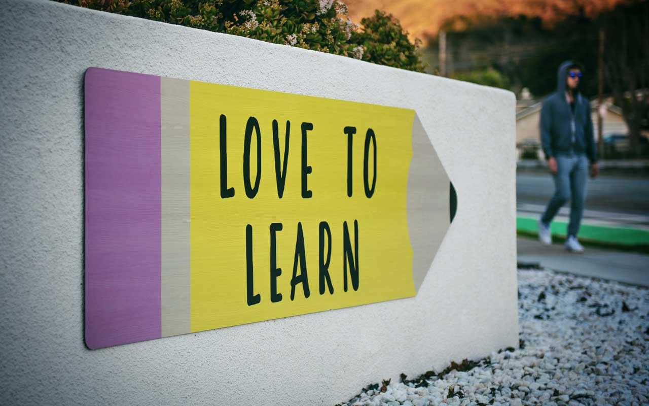 "A sign reads ""love to learn,"" drawn over a large yellow pencil."